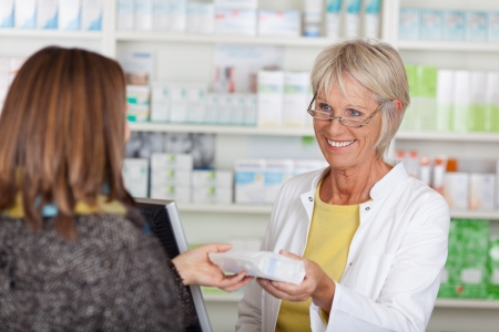 Happy senior female pharmacist giving prescribed medicine to customer in pharmacy photo