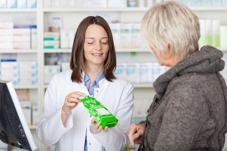 drugstore: Farmacéutico de sexo femenino que explica los detalles del producto a los clientes en farmacia