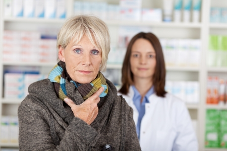 Portrait of unwell senior woman in sweater with pharmacist in background at pharmacy photo