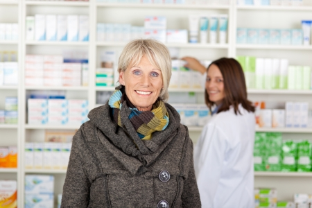 Senior with a scarf in the pharmacy with the pharmacist in the background photo