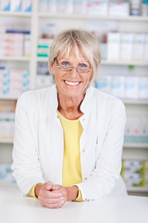 Portrait of a pharmacist in the pharmacy leaning on the desk photo