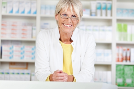 Portrait of confident female pharmacist smiling while leaning on counter in pharmacy