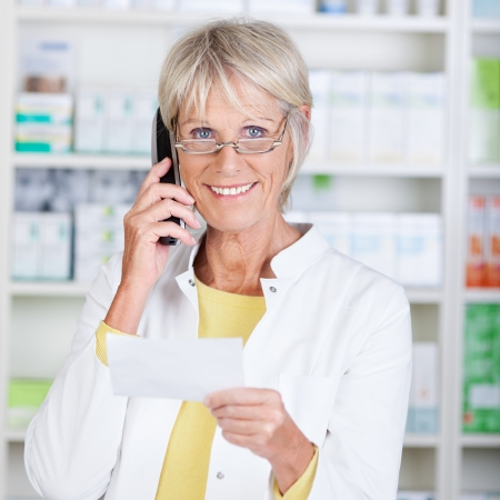 cordless phone: Portrait of happy senior pharmacist using cordless phone while holding prescription paper in pharmacy