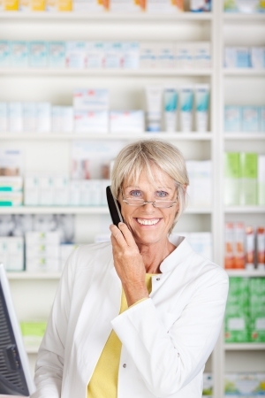 Smiling senior pharmacist talking to customer on the telephone photo