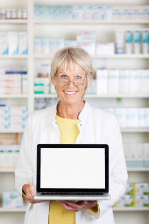 Portrait of happy female pharmacist displaying laptop in pharmacy Stock Photo