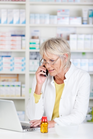 Pharmacist having a call and looking at laptop photo