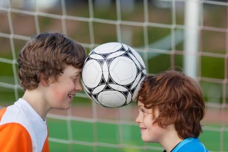 portret van twee jonge vrienden balanceren voetbal bal tussen hoofden Stockfoto