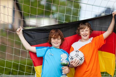 soccer fan: Portrait of happy boys with trophy and soccer ball holding German flag against net Stock Photo