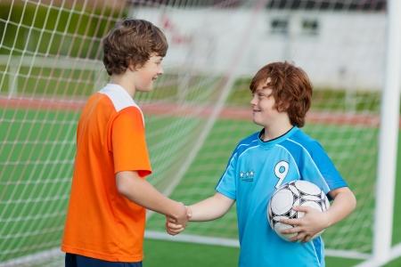 congratulate: Little boys shaking hands against net on soccer field Stock Photo