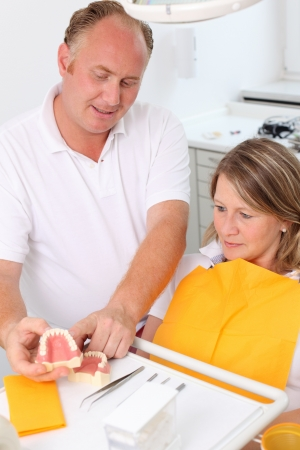 Male dentist explaining a female patient denture work in dental clinic photo