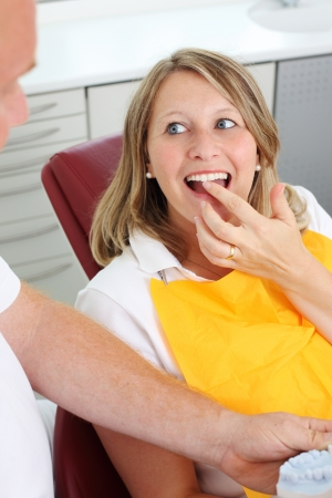 molds: Portrait of female patient showing her teeth to dentist in dental clinic