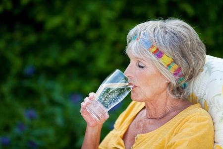 Senior woman with eyes closed drinking sparkling water in park photo