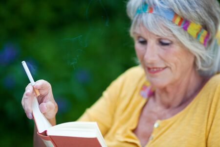 Senior woman reading book while smoking cigarette at park photo