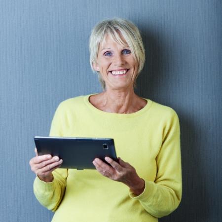 mujeres ancianas: Retrato de una mujer mayor que trabaja en una tablilla y sonriente.