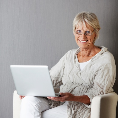 Portrait of happy senior woman with laptop sitting on couch against grey wall photo