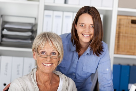 Twee generaties, jongere en oudere vrolijk poseren binnen het kantoor. Stockfoto - 21260851