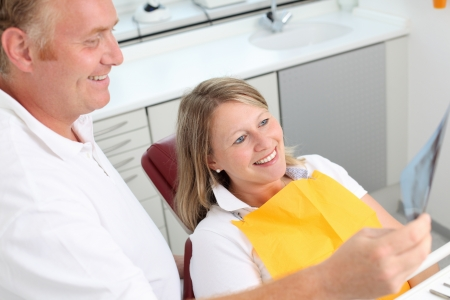 Happy dentist and female patient analyzing Xray in clinic Stock Photo - 21260853