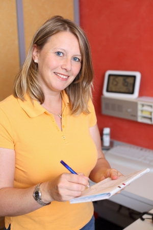 Portrait of confident female dentist writing on document at desk in clinic photo