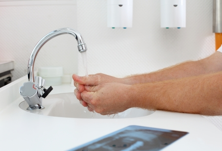 dentalcare: Cropped image dentist washing hands at clinic Stock Photo
