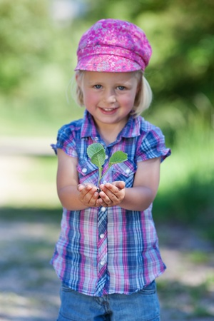 Sweet girl smiling and holding a little plant on her hands photo
