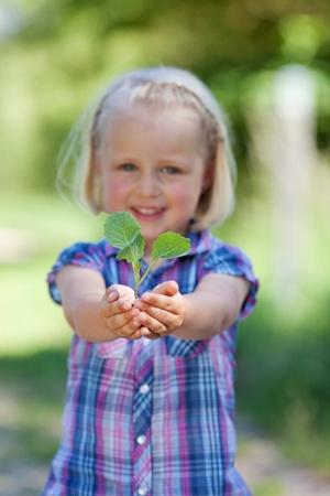 Chica joven que sonríe y que sostiene una pequeña planta en sus manos Foto de archivo