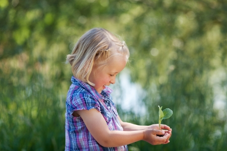 Young cheerful girl holding a little plant on her hands