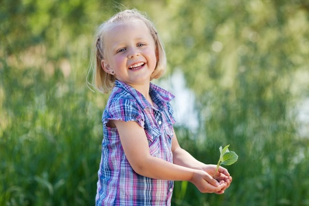 Happy young child holding a little plant on her hands photo