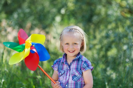 Happy beautiful little blond girl with a large pinwheel or toy windmill in the colours of the rainbow standing outdoors against greenery photo