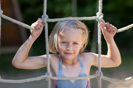 Girl climbs a rope net at a playground photo
