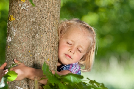 loves: Little girl loves her tree and is hugging the trunk Stock Photo