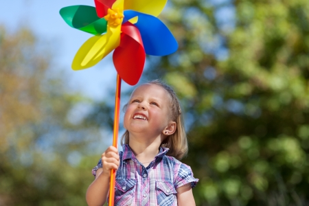 Cute little girl watching a colourful pinwheel or toy windmill in the colours of the rainbow waiting for it to turn in the wind photo