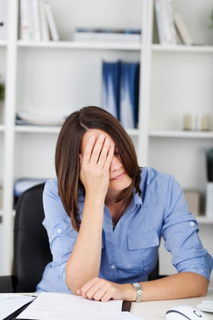 Despondent businesswoman sitting at her desk resting her head in her hand covering her eyes photo