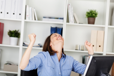 jubilation: Businesswoman rejoicing in her office sitting at her desk with her head tilted back and a big smile of jubilation and her clenched fists raised in the air Stock Photo