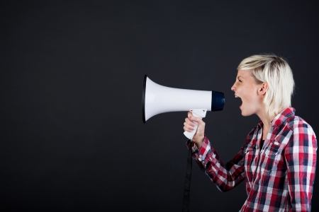 Side view of a young blond woman shouting into the megaphone against black background