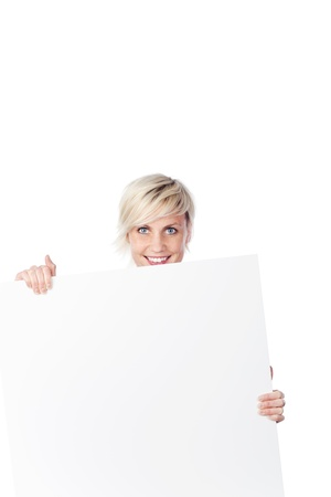 Portrait of a smiling young woman holding a empty board against white background photo