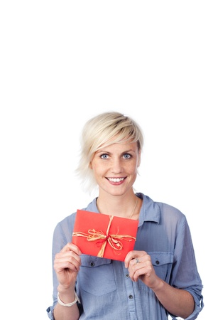 Portrait of a smiling young woman holding gift coupon against white background photo