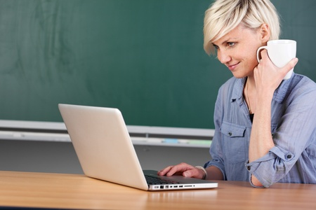 Young female teacher with laptop and coffee cup sitting at school table Stock Photo - 21264905