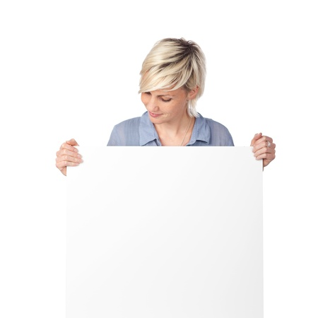 Young blond woman looking at white sign against white background photo