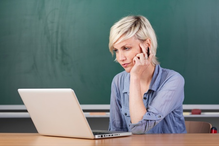 Serious young female teacher using laptop at school table Stock Photo - 21264913