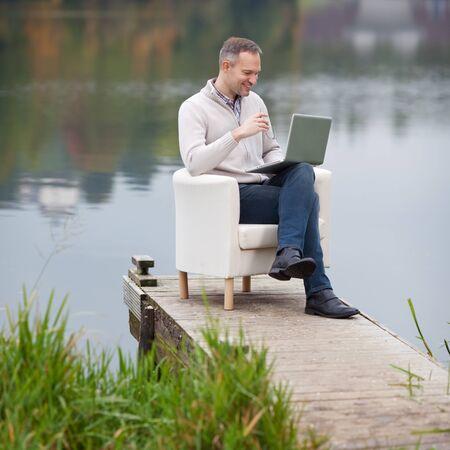 Ver en el hombre sonriente maduros usando la computadora portátil en el muelle
