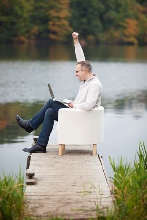arm chair: Full side view of excited mature man celebrating victory while using laptop on pier