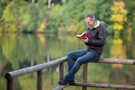 man holding book: Full length of mature man reading book while sitting on fence against lake Stock Photo