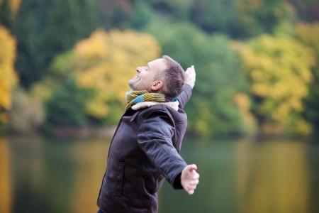 persona feliz: Vista lateral de un hombre maduro con los brazos extendidos de pie en el muelle Foto de archivo