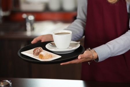 hospitality: close-up of a waitress serving a cup of coffee and snacks Stock Photo
