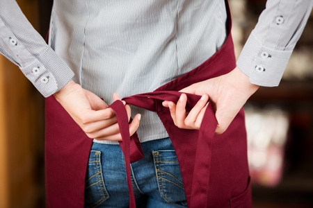 Rear midsection of waitress tying apron in cafe 免版税图像
