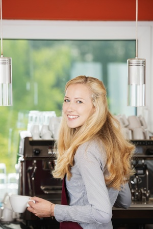 Portrait of happy waitress holding coffee cup against machine in cafe photo