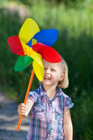 Smiling little girl with a colourful pinwheel or toy windmill looking at it an anticipation as she waits for the breeze photo