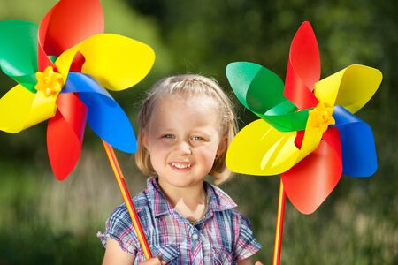 Cute little girl holding two large colourful rainbow coloured toy windmills in her hands outdoors photo