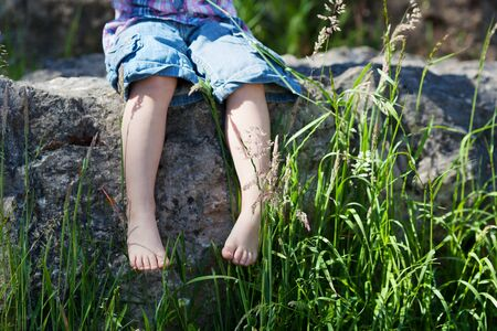 Conceptual image of a young nature lover with a closeup view of the barefoot legs of a little girl dangling over a stone wall with reeds and greenery photo