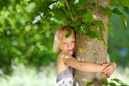 La niña está abrazando el tronco de un árbol Foto de archivo